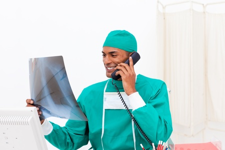torax: Smiling doctor on phone examining an x-ray  Stock Photo