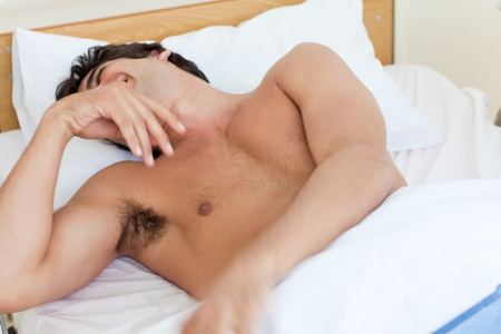 Attractive barechested man laughing on a bed  photo