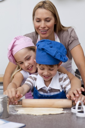 Mother and children baking cookies in the kitchen photo