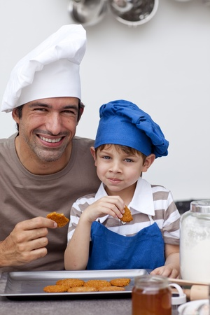 Father and son eating biscuits in the kitchen photo
