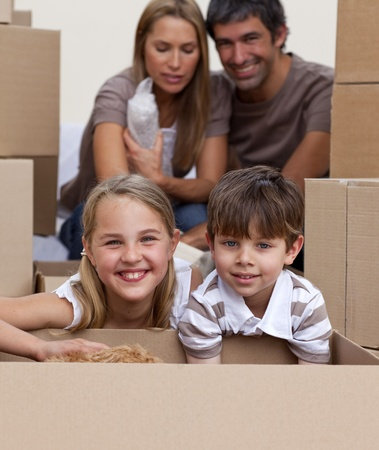 Portrait of children unpacking boxes with their parents photo
