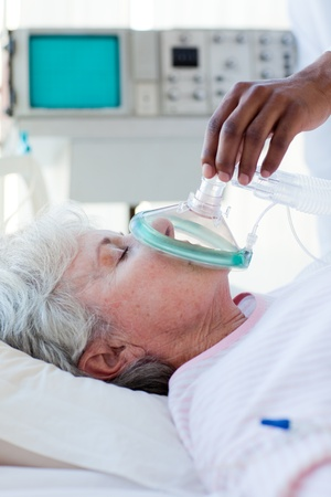 A doctor putting oxygen mask on a patient Stock Photo - 10115187