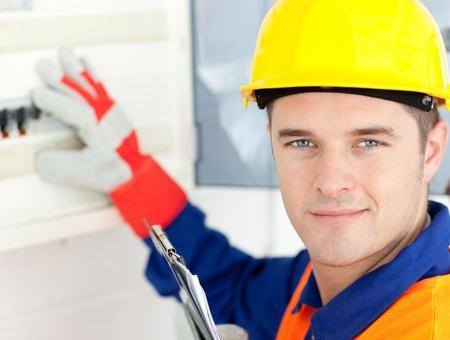 Smiling electrician repairing a power plan photo