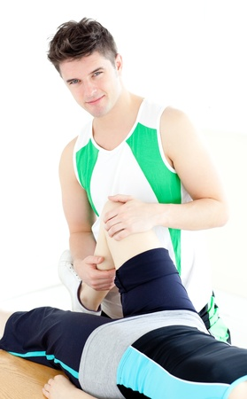 Young male physical therapist checking a womans knee  photo