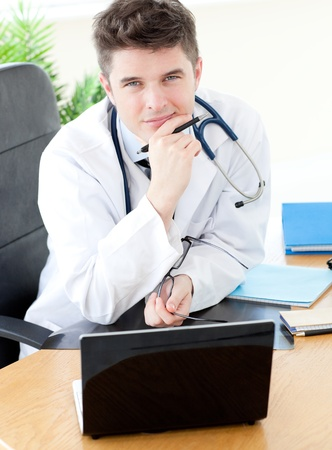 Smiling male doctor using a laptop sitting at his desk  photo