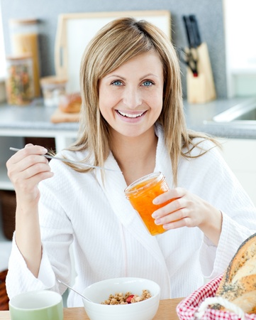 gratified: Young woman having breakfast in the kitchen