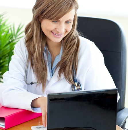 Bright female doctor working with a laptop  photo