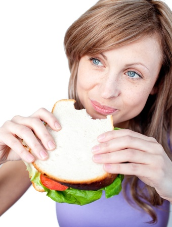 unhealthy snack: Cheerful woman eating a sandwich