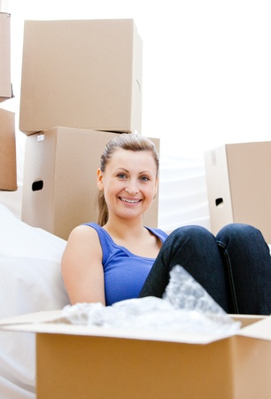 gratified: Smiling woman having a break between boxes
