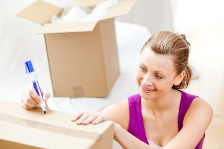 gratified: Happy woman writing on boxes using a pen