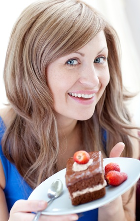 Cheerful woman holding a piece of chocolate cake  Stock Photo - 10129256