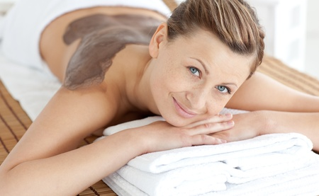 Beautiful woman enjoying a mud skin treatment photo