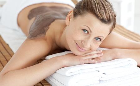 spa treatment: Beautiful woman enjoying a mud skin treatment