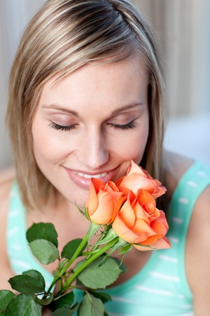 Cheerful woman smelling roses photo