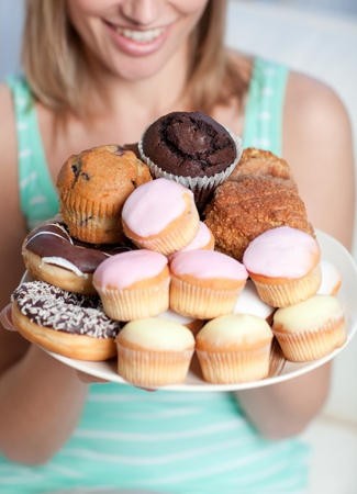 Blond woman holding a plate of cakes photo