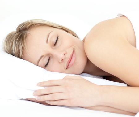 Strålande kvinna sover på sin säng Stockfoto