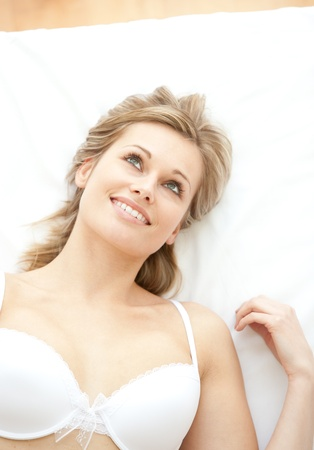 Bright woman in underwear lying on bed photo