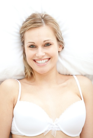 Smiling woman in underwear lying on bed photo