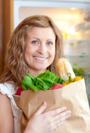 grocer: Radiant woman holding a grocery bag