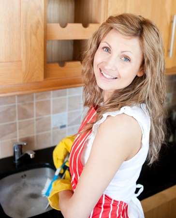 stereotypical: Positive woman doing the dishes