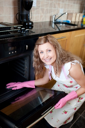 Smiling woman cleaning the oven photo