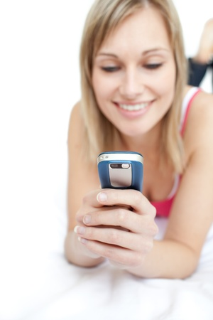 Young woman sending a text lying on a bed  Stock Photo - 10109190