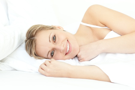 Jolly woman relaxing lying on a bed photo