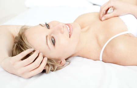 Charming woman relaxing lying on her bed  photo