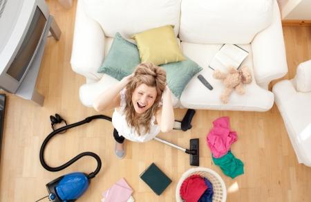 Gestresst, blonde Frau, Staubsaugen im Wohnzimmer Lizenzfreie Bilder
