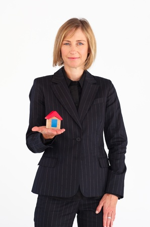 Mature businesswoman holding a house photo