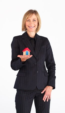 Mature businesswoman presenting a model of house photo