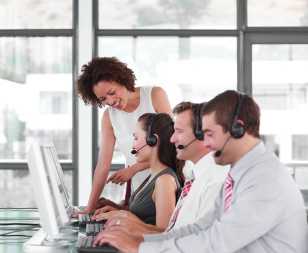 Smiling female leader managing he team in a call center photo