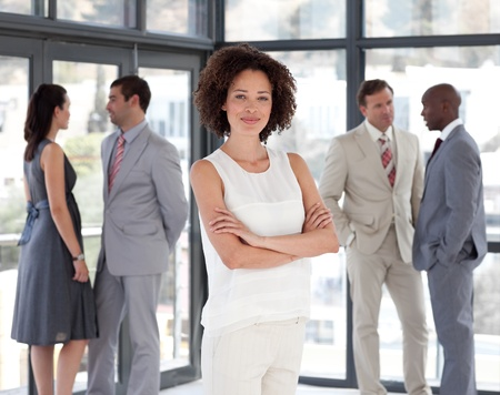ethnic diversity: Serious female leader with her team Stock Photo