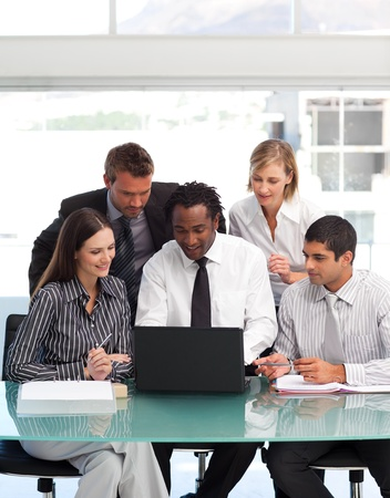 Business people using a laptop together photo