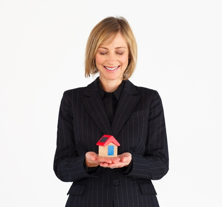 Smiling mature businesswoman presenting a model of house against a white background photo