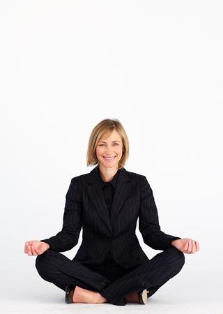 Smiling mature businesswoman doing yoga exercises  photo