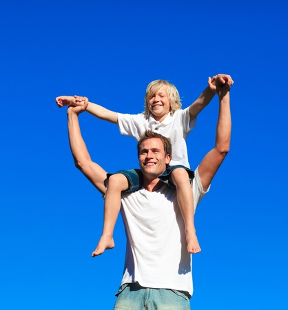 Child sitting on his fathers shoulders photo