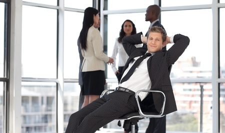 manager relaxing in office with team in background  Stock Photo - 10113035