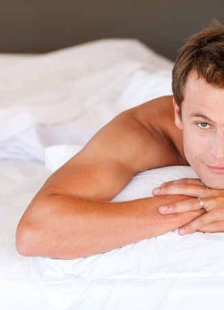 Young man relaxing in bed looking at the camera photo