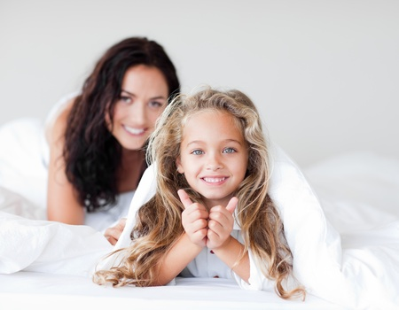 Attractive mother and daugther embracing on bed Stock Photo - 10114405