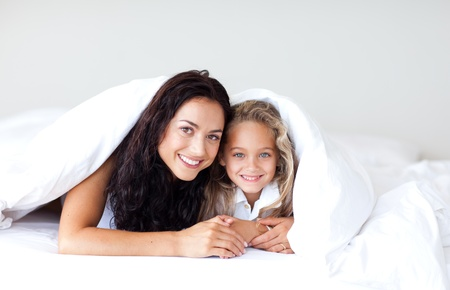 Cute mother and daugther having fun on bed  photo