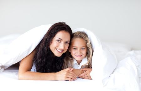 woman bed: Linda madre e hija divertirse en la cama