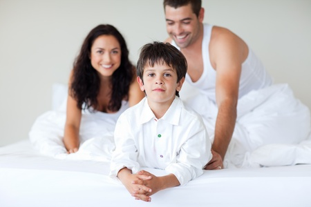 Young couple and son playing in bed photo