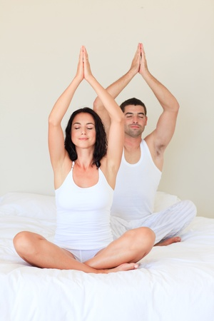 Couple doing exercises on bed with closed eyes photo