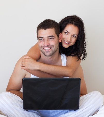 Smiling couple using a laptop on a bed