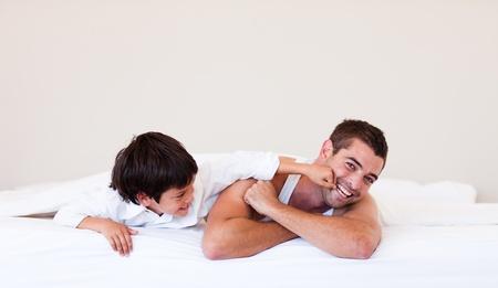 padre e hijo: Padre y su hijo que se divierten en una cama Foto de archivo
