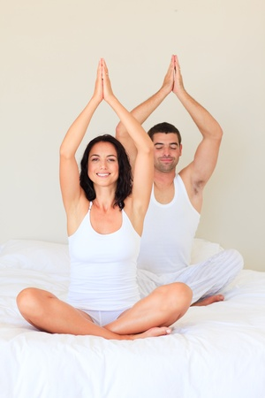 Couple sitting on bed in meditation pose photo