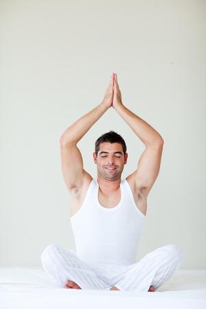 Man sitting on bed doing meditation exercises photo