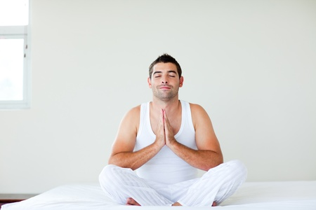 Man sitting on bed meditating with clossed eyes photo