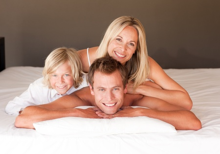 Beautiful family having fun together lying on bed photo